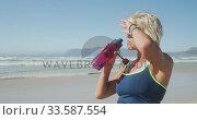 Купить «Athletic woman drinking water on the beach», видеоролик № 33587554, снято 30 января 2020 г. (c) Wavebreak Media / Фотобанк Лори