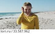 Купить «Woman standing on the beach and looking at camera», видеоролик № 33587962, снято 21 ноября 2019 г. (c) Wavebreak Media / Фотобанк Лори