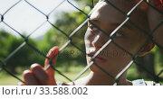 Купить «Mixed race woman looking through a fence », видеоролик № 33588002, снято 10 января 2020 г. (c) Wavebreak Media / Фотобанк Лори