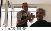 Купить «Low angle view woman having her hair cut by a hairdresser», видеоролик № 33588694, снято 29 апреля 2019 г. (c) Wavebreak Media / Фотобанк Лори