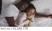 Купить «African american father and daughter sleeping together », видеоролик № 33589170, снято 14 января 2020 г. (c) Wavebreak Media / Фотобанк Лори