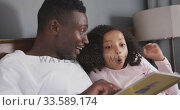 Купить «African american father reading a story to his daughter in bed», видеоролик № 33589174, снято 14 января 2020 г. (c) Wavebreak Media / Фотобанк Лори