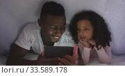 Купить «African american father and daughter looking at phone in bed », видеоролик № 33589178, снято 14 января 2020 г. (c) Wavebreak Media / Фотобанк Лори