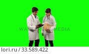 Купить «Front view doctors checking their results on digital tablet with green screen», видеоролик № 33589422, снято 18 января 2019 г. (c) Wavebreak Media / Фотобанк Лори