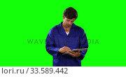 Купить «Front view of mechanic taking note with green screen», видеоролик № 33589442, снято 18 января 2019 г. (c) Wavebreak Media / Фотобанк Лори