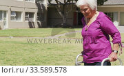 Senior woman walking in the park of a retirement home. Стоковое видео, агентство Wavebreak Media / Фотобанк Лори