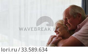 Senior couple in social distancing hugging each other in retirement house. Стоковое видео, агентство Wavebreak Media / Фотобанк Лори