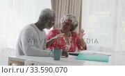 Купить «A senior african american couple spending time together at home working on papers. social distancing», видеоролик № 33590070, снято 12 ноября 2019 г. (c) Wavebreak Media / Фотобанк Лори