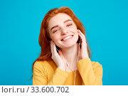 Купить «Lifestyle concept - Portrait of cheerful happy ginger red hair girl enjoy listening to music with headphones joyful smiling to camera. Isolated on Blue Pastel Background. Copy space.», фото № 33600702, снято 6 августа 2020 г. (c) easy Fotostock / Фотобанк Лори
