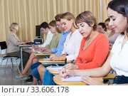 Купить «Side view of young people with female lecturer in auditorium», фото № 33606178, снято 7 июня 2020 г. (c) Яков Филимонов / Фотобанк Лори