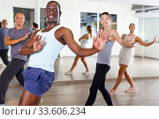 Купить «Cheerful people practicing vigorous lindy hop movements in dance class», фото № 33606234, снято 30 июля 2018 г. (c) Яков Филимонов / Фотобанк Лори