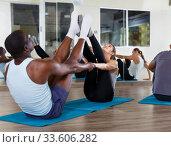 Купить «People doing stretching exercises in pairs», фото № 33606282, снято 30 июля 2018 г. (c) Яков Филимонов / Фотобанк Лори