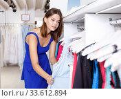 Купить «Girl choosing new clothes in showroom», фото № 33612894, снято 17 сентября 2018 г. (c) Яков Филимонов / Фотобанк Лори