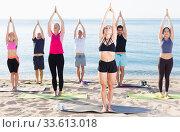 Купить «Sporty people practicing yoga on beach», фото № 33613018, снято 14 июня 2017 г. (c) Яков Филимонов / Фотобанк Лори