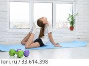Девочка выполняет растяжку мышц спины занимаясь дома. Стоковое фото, фотограф Иванов Алексей / Фотобанк Лори