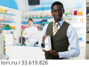 Satisfied African American man standing in drugstore. Стоковое фото, фотограф Яков Филимонов / Фотобанк Лори
