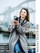 Купить «woman with luggage posing at quay and smiling», фото № 33619906, снято 27 марта 2017 г. (c) Яков Филимонов / Фотобанк Лори