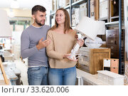 Купить «Girl with boyfriend in search of table lamp», фото № 33620006, снято 9 ноября 2017 г. (c) Яков Филимонов / Фотобанк Лори