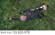 Vertical footage top view of gardener working in green yard during seasonal landscaping. Worker cutting grass in garden, using gasoline lawn trimmer for cutting turf. Редакционное видео, видеограф А. А. Пирагис / Фотобанк Лори