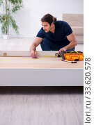 Купить «Young male contractor installing furniture at home», фото № 33620578, снято 11 ноября 2019 г. (c) Elnur / Фотобанк Лори