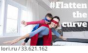 Купить «Caucasian woman wearing cape holding her daughter with words #Flatten the Curve during coronavirus c», фото № 33621162, снято 3 августа 2020 г. (c) Wavebreak Media / Фотобанк Лори