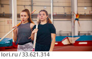 Pole vault training - two women standing on the stadium holding their poles and looking in the camera. Стоковое фото, фотограф Константин Шишкин / Фотобанк Лори