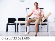 Купить «Young injured man waiting for his turn in hospital hall», фото № 33621686, снято 3 мая 2019 г. (c) Elnur / Фотобанк Лори