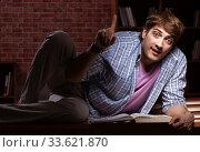 Купить «Young handsome student preparing for exams at night», фото № 33621870, снято 28 августа 2018 г. (c) Elnur / Фотобанк Лори