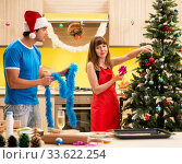 Young couple celebrating Christmas in kitchen. Стоковое фото, фотограф Elnur / Фотобанк Лори
