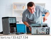 The young technician repairing computer in workshop. Стоковое фото, фотограф Zoonar.com/Elnur Amikishiyev / easy Fotostock / Фотобанк Лори