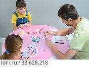Семья играет за столом в настольные игры, вид сверху. Стоковое фото, фотограф Иванов Алексей / Фотобанк Лори