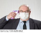 Купить «Close up portrait of handsome man in a protective medical mask  and glasses with IR thermometer», фото № 33628662, снято 24 апреля 2020 г. (c) Михаил Котов / Фотобанк Лори