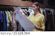 Купить «Portrait happy woman choosing new clothes on hangers in shop», видеоролик № 33628954, снято 4 августа 2020 г. (c) Яков Филимонов / Фотобанк Лори