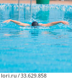 Купить «Young girl in goggles and cap swimming butterfly stroke style in the blue water pool», фото № 33629858, снято 10 июля 2020 г. (c) age Fotostock / Фотобанк Лори