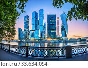 """Москва-Сити"" вечером. Moscow City skyscrapers in a frame of green trees (2017 год). Стоковое фото, фотограф Baturina Yuliya / Фотобанк Лори"