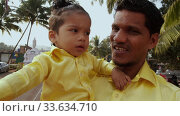 Arambol, Goa, India - December 30, 2019: A man with a child in her arms in yellow shirts is smiling at the camera. Редакционное видео, видеограф Aleksandr Lutcenko / Фотобанк Лори