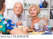 Happy mature couple drinking tea with female guest. Стоковое фото, фотограф Яков Филимонов / Фотобанк Лори