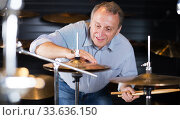Купить «Musician male choosing drum set», фото № 33636150, снято 18 сентября 2017 г. (c) Яков Филимонов / Фотобанк Лори
