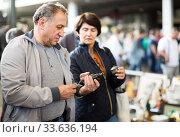 Happy mature spouses buying retro handicrafts on flea market. Стоковое фото, фотограф Яков Филимонов / Фотобанк Лори