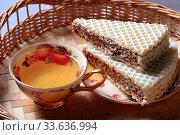 Купить «Cup of tea and waffles with chocolate filling close-up», фото № 33636994, снято 27 апреля 2020 г. (c) Яна Королёва / Фотобанк Лори