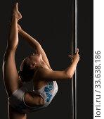 Pole dance. Flexible girl doing vertical split. Стоковое фото, фотограф Гурьянов Андрей / Фотобанк Лори