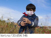Young boy with a mask play in the field after 45 days at home without being able to leave as a measure of confinement for the Covid-19 on April 27, 2020... Редакционное фото, фотограф Manuel Cedron / age Fotostock / Фотобанк Лори