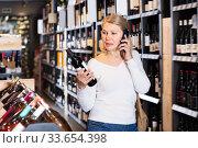 Купить «Glad woman talking on phone in wine store», фото № 33654398, снято 6 августа 2020 г. (c) Яков Филимонов / Фотобанк Лори