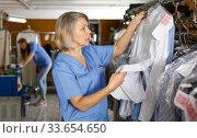 Купить «Dry-cleaning salon worker», фото № 33654650, снято 22 января 2019 г. (c) Яков Филимонов / Фотобанк Лори