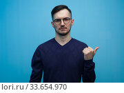 Купить «Positive young man in casual clothes and glasses points with his finger something useful on blue background», фото № 33654970, снято 14 апреля 2019 г. (c) Pavel Biryukov / Фотобанк Лори