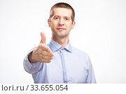 Купить «successful friendly man pulls his hand to say hello, for a snooto, in a blue light casual shirt staring at the camera. Isolated», фото № 33655054, снято 22 апреля 2020 г. (c) Владимир Арсентьев / Фотобанк Лори