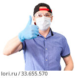 Portrait of delivery man gesturing wearing thumb up sign, wearing safety glasses, surgical mask and blue neoprene gloves, solated on white background. Стоковое фото, фотограф Кекяляйнен Андрей / Фотобанк Лори