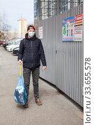 Купить «Adult man taking out garbage during coronavirus pandemic, it is allowed without any permission. Inscription on plate in Russian: trush enclosure and attention videosurveillance», фото № 33655578, снято 24 апреля 2020 г. (c) Кекяляйнен Андрей / Фотобанк Лори