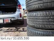 Close up view of summer tire with open trunk of passenger car, seasonal wheel change. Стоковое фото, фотограф Кекяляйнен Андрей / Фотобанк Лори