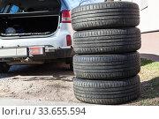 Купить «Four summer tyres are next to opened trunk of suv car, seasonal tire change», фото № 33655594, снято 22 апреля 2020 г. (c) Кекяляйнен Андрей / Фотобанк Лори